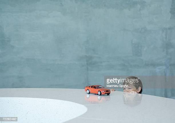 boy peeking at toy sports car - peeking stock pictures, royalty-free photos & images