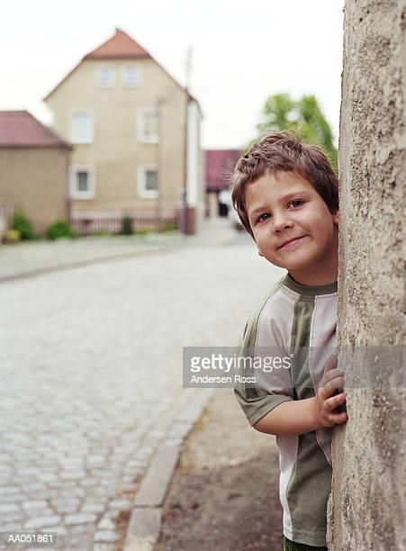 Boy (4-6) peeking from behind wall (selective focus)