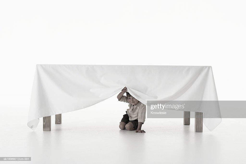 Boy (4-5 years) peeking from under tablecloth, studio shot, portrait : Stockfoto