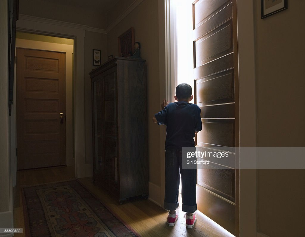 Boy peeking into room with light coming out : Stock Photo