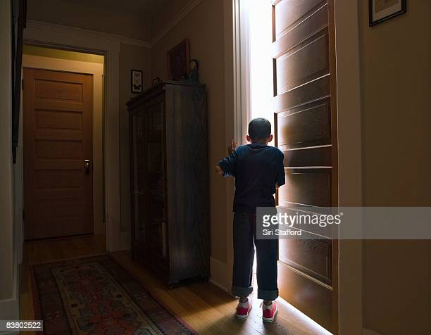 boy peeking into room with light coming out - doorway stock pictures, royalty-free photos & images