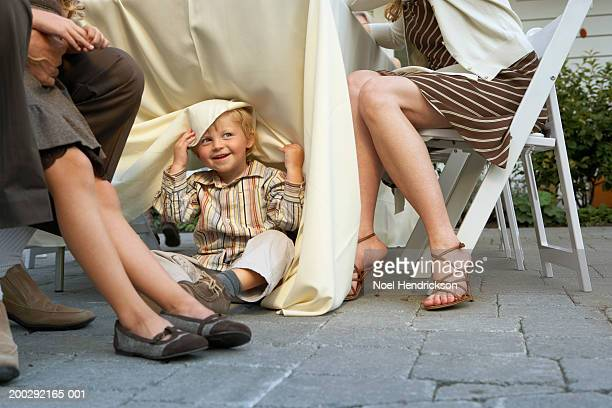 Boy (2-4 years) peeking out from beneath table cloth of dining table on patio