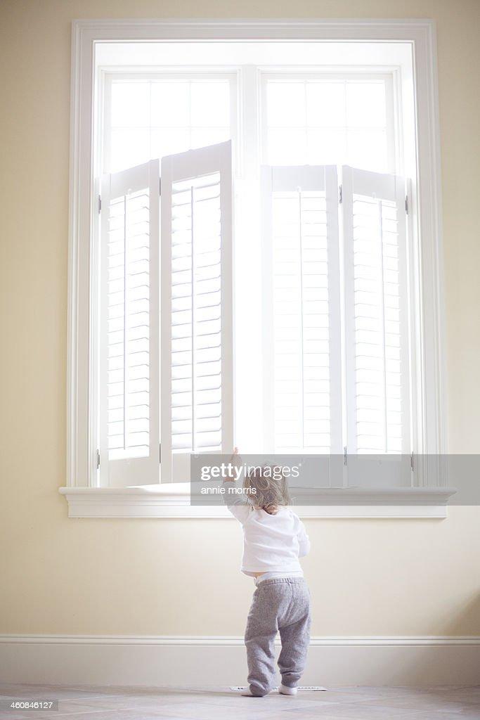 Boy peeking out window : Stock Photo