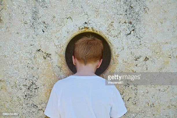 boy peeking through hole in wall - peeping holes ストックフォトと画像