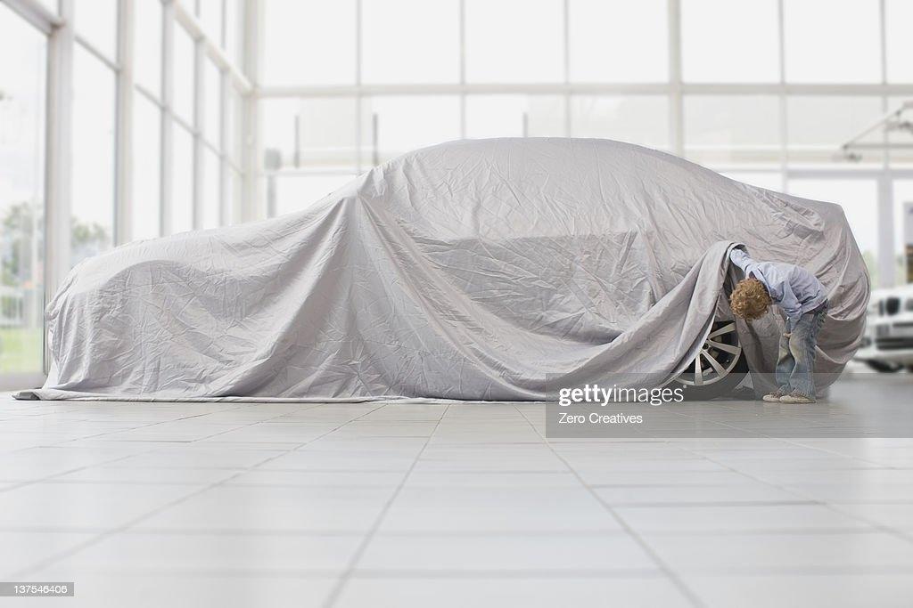 Boy peeking under cloth on car : Stock Photo