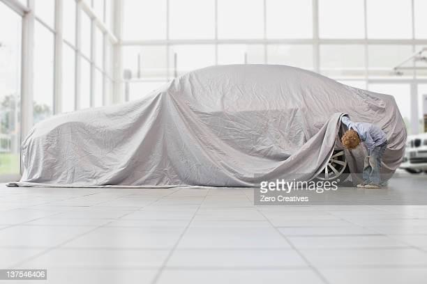 Boy peeking under cloth on car