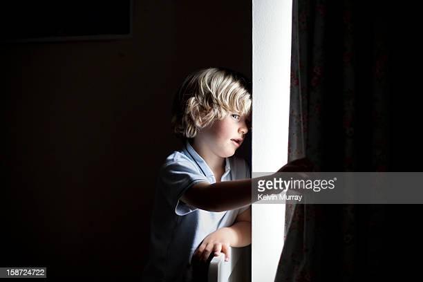 Boy peeks through window curtains