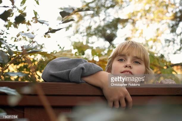 Boy (10-11) peeping over fence