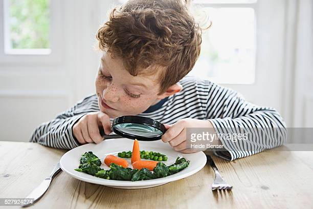 Boy (7-9) peering over magnifying glass on dinner