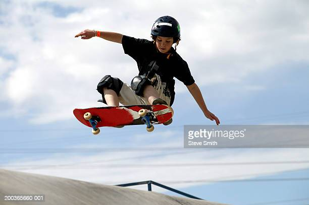 Boy (9-11) performing jump on skateboard, low angle view