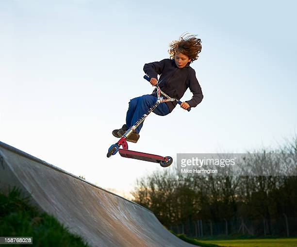 Boy performing micro scooter trick at skate park.