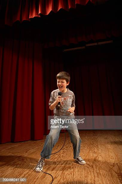 Boy (8-10) performing on stage, singing into microphone