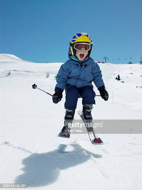 Boy (5-7) performing ski jump on snow covered slope, mouth open