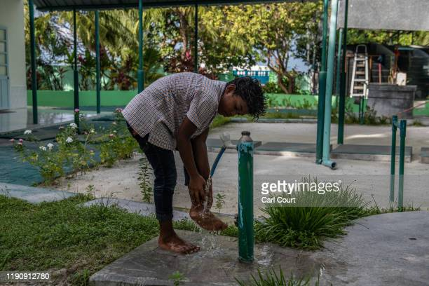 A boy performs ablutions using groundwater before praying at a mosque on December 16 2019 in Mahibadoo Maldives The Maldives is the worlds lowest...
