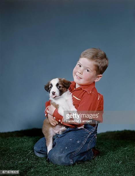 boy petting his puppy  - mamífero con garras fotografías e imágenes de stock