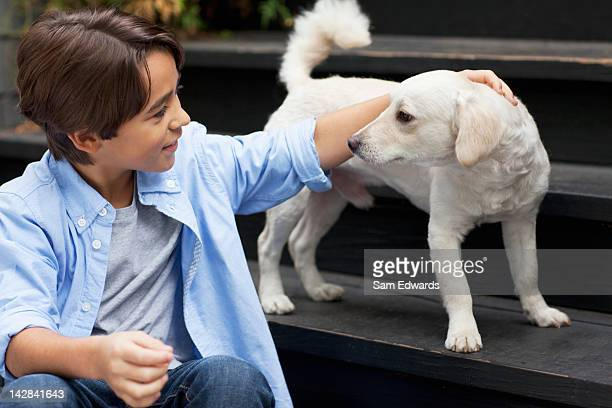 Boy petting puppy on steps outdoors