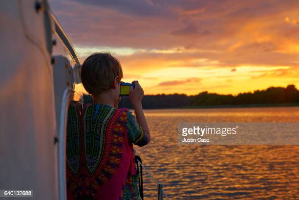 Boy photographing beautiful sunset on a lake from his boat