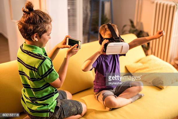 Boy photographing brother who is playing with virtual reality simulator.