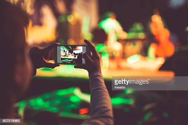 Boy photographing event with mobile phone