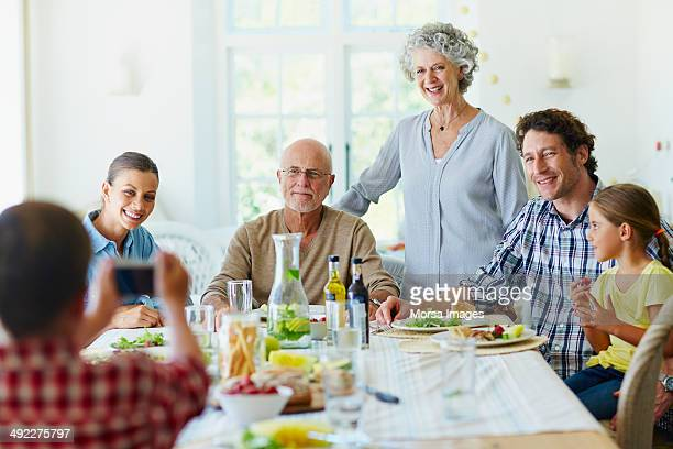 Boy photographing family at dining table