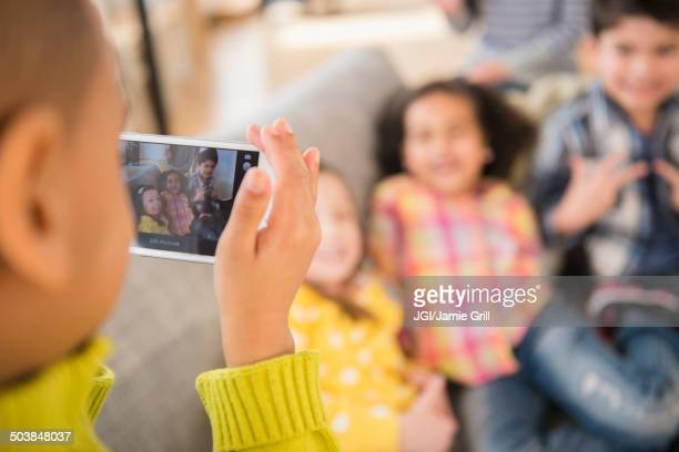Boy photographing friends on sofa