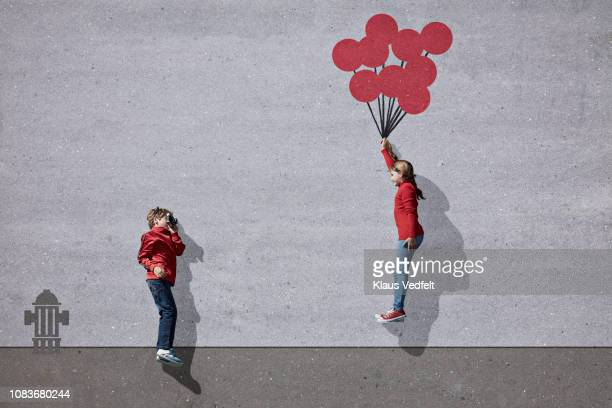 Boy photographing girl holding imaginary painted ballons
