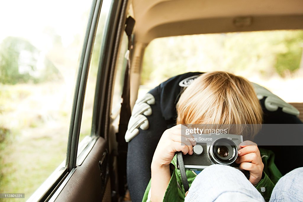 Boy photographing in back seat of car : Stock Photo