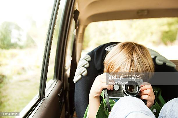 Boy photographing in back seat of car