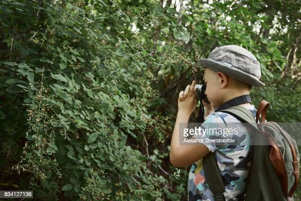 Boy photographing in forest
