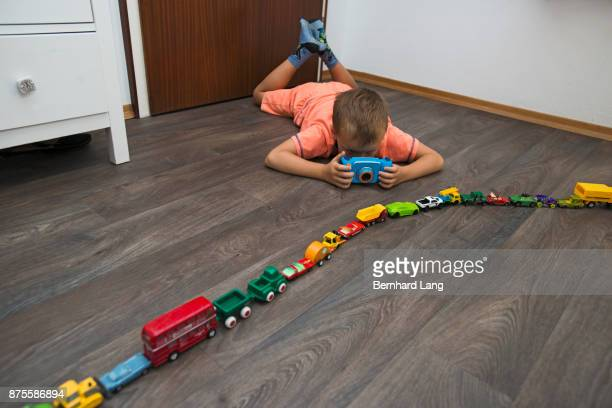Boy photographing toy cars on the floor