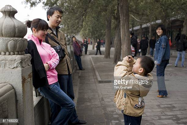 Boy photographs parents at Summer Palace Beijing China has a one child family planning policy to limit population