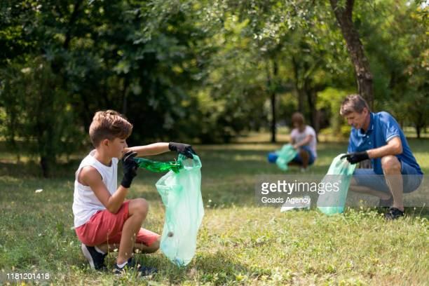 boy picking litter - responsibility stock pictures, royalty-free photos & images