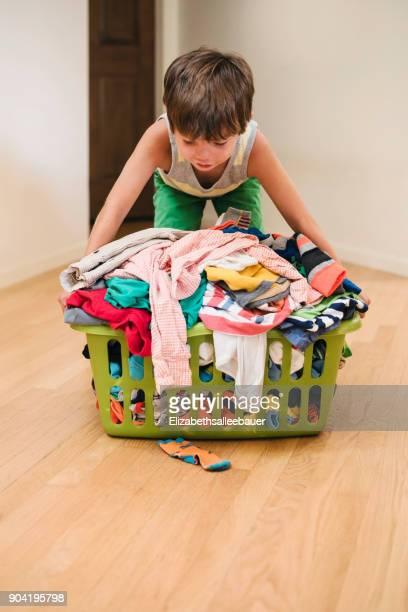 Boy picking up a full laundry basket