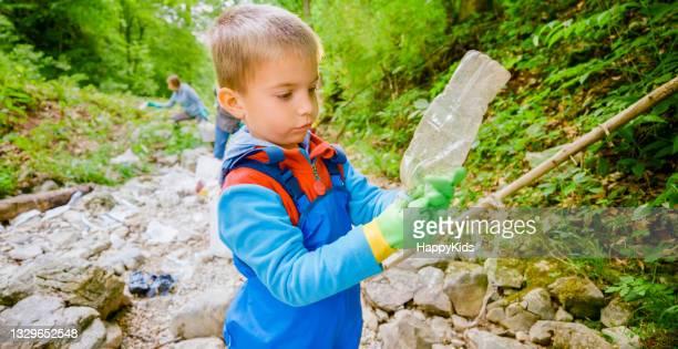 boy picking up crushed plastic bottle