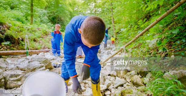 boy collecting plastic rubbish bucket forest