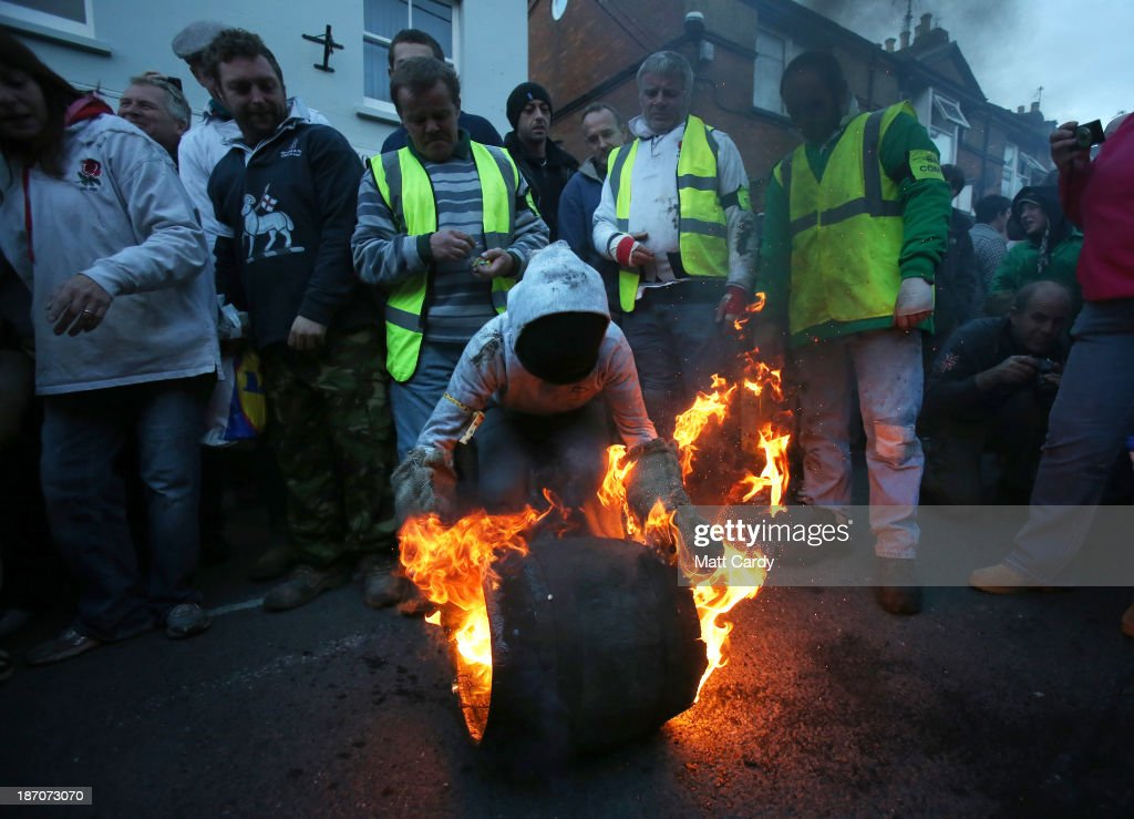 A boy picks up a burning barrel soaked in tar at the annual Ottery St Mary Tar Barrel festival on November 5 2013 in Ottery St Mary, Devon, England. The tradition, which is over 400 years old, sees competitors (who must have been born in the town to take part) running with burning barrels on their backs through the village, until the heat becomes too unbearable or the barrel breaks down, starting with junior barrels carried by children and continuing all evening with ever larger and larger barrels. The event, which has been threatened with closure on previous years, raises thousands of pounds for charity and attracts spectators from around the world.