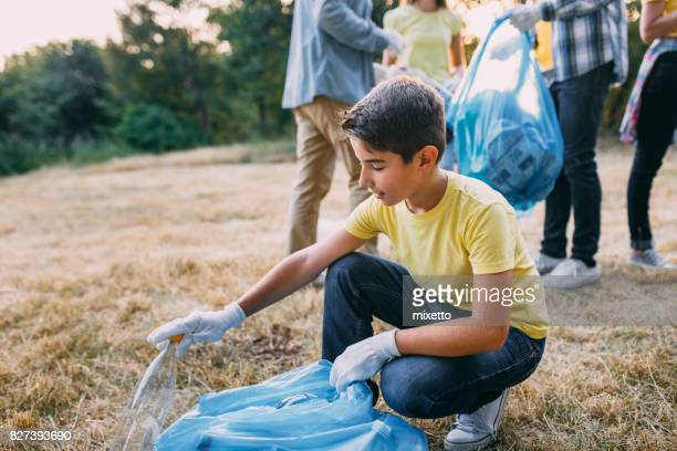 Boy picks up a trash in a park