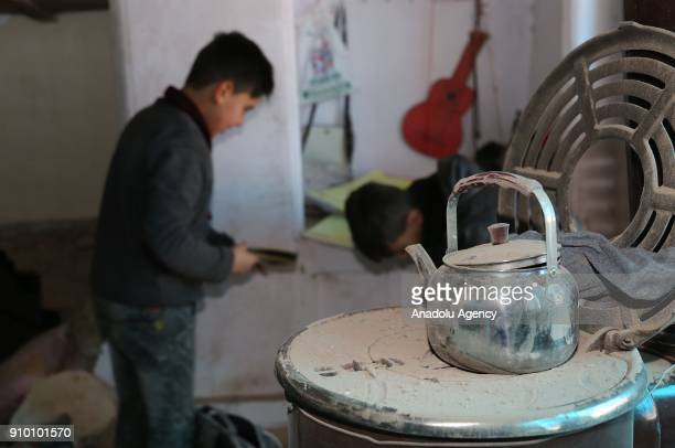 A boy picks up his belongings at his damaged house after a rocket fired by PYD/PKK terrorists from Syria's Afrin hit a house belonging to a Syrian...