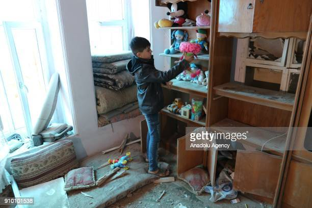 A boy picks up his toys at his damaged house after a rocket fired by PYD/PKK terrorists from Syria's Afrin hit a house belonging to a Syrian family...