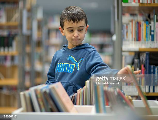 A boy pics out a children's book during the presentation of Project 'Lesestart' in a Libary for Children on November 15 2013 in Berlin Germany The...