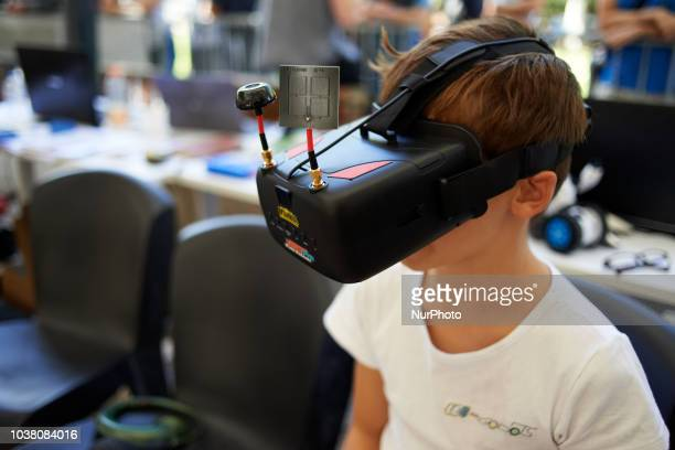 A boy pilots a robot car with a VR headset A robots race took place in Toulouse Machines are either cars or walking robots They were supposed to run...
