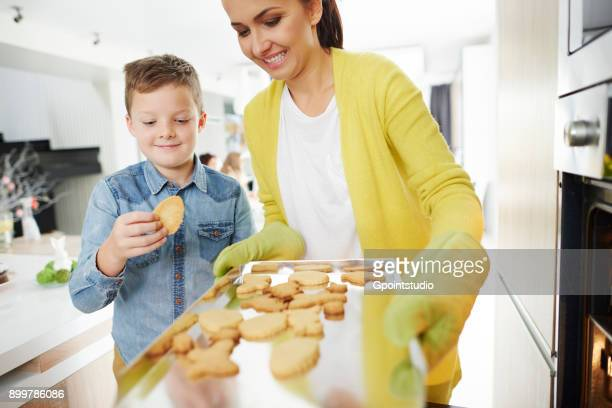 boy pinching easter biscuit from mothers baking tray in kitchen - happy easter mom ストックフォトと画像