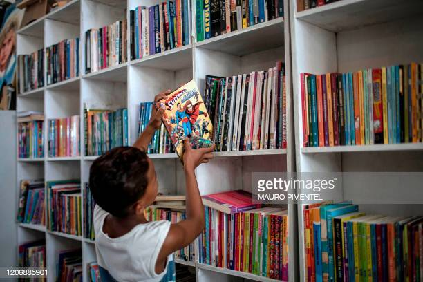 A boy places a book on a shelve of the public library Mundo da Lua founded by Brazilian 12yearold Lua Oliveira five months ago at the Tabajaras...