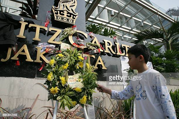 A boy places a flower on the RitzCarlton hotel in Jakarta on July 18 2009 while investigators probe the twin bombing a day after two explosions tore...