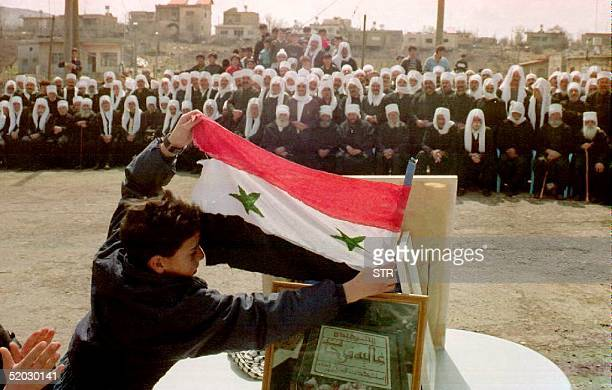 Boy places a Syrian flag in front of thousands of Druze demonstrating 16 March, 1993 in Bukata. The Druze were protesting the 15 March 1993 shooting...