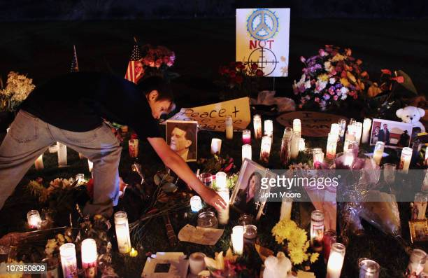 A boy places candle at a makeshift shrine at the University Medical Center for those killed and wounded during an attack on US Rep Gabrielle Giffords...