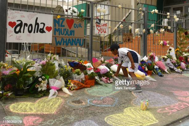 A boy places Flowers outside a Mosque in Kilbirnie Wellington on March 16 2019 in Kilbirnie New Zealand At least 49 people are confirmed dead with...