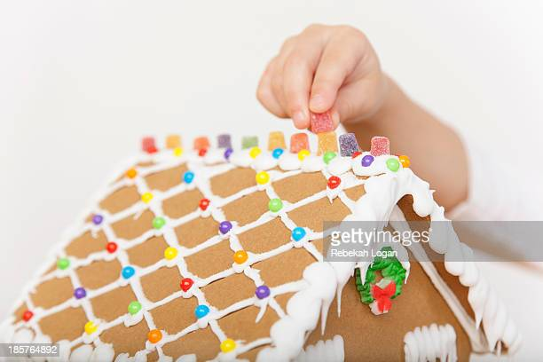 Boy placing candy on gingerbread house.