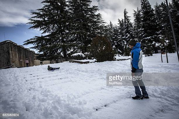 Boy play in L'Aquila, Italy, on January 19, 2017. A great deal of snow has fallen in the area, which was hit by four quakes on Wednesday. Four strong...