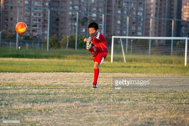 a boy play soccer game in a field - trefferversuch stock-fotos und bilder
